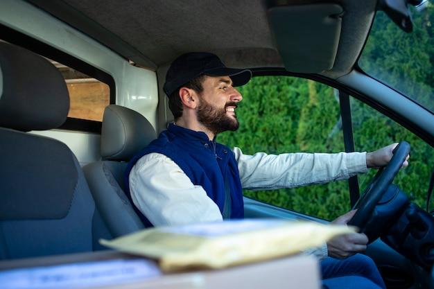 Служба быстрой доставки и улыбающийся курьер с грузом за рулем своего фургона.