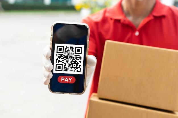 소포 우편함을 들고 있는 빠른 배달 서비스 남자는 집에서 온라인 결제, 빠른 배달 서비스, 속달 배달, 온라인 쇼핑 개념을 위해 휴대폰에서 고객 스캔 qr 코드를 기다리고 있습니다.