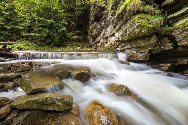 明るく晴れた夏の日に、美しい滝の大きな石から落ちる滑らかな絹のような水で速く流れる川の流れ。