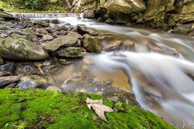 明るい日当たりの良い夏の日に美しい滝の大きな石から落ちる滑らかな絹のような水で速く流れる川の流れ。