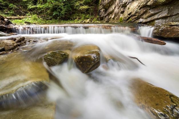 Быстрый поток реки с гладкой шелковистой водой, падающей с больших камней в красивых водопадах в яркий солнечный летний день.