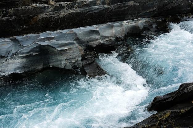 日光の下で崖と岩に囲まれた速く流れる小川