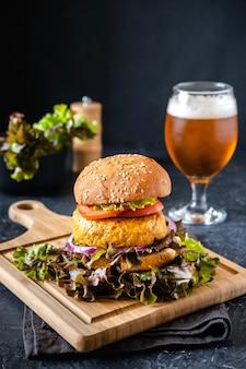ファストフード。大きなハンバーガーとビールのグラス。暗い背景に。