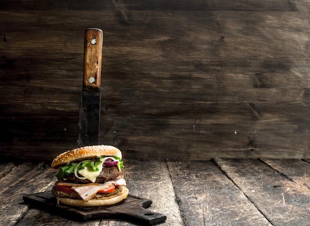 패스트 푸드. 큰 칼로 쇠고기와 야채로 만든 신선한 버거. 나무 배경.