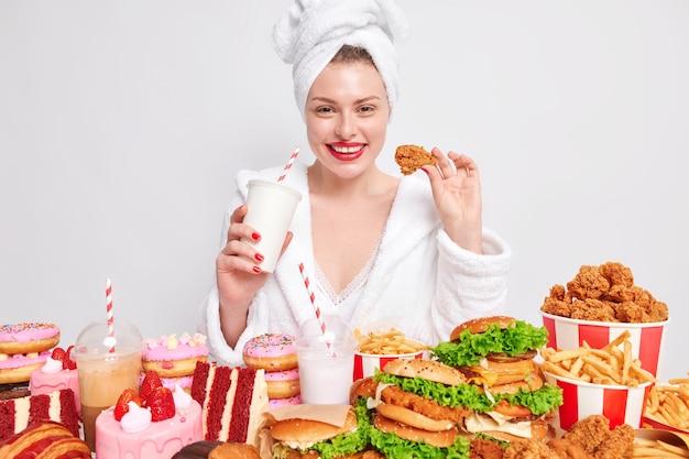 Концепция быстрого питания и переедания. улыбающаяся молодая женщина с красными губами ест наггетсы, пьет газированный напиток
