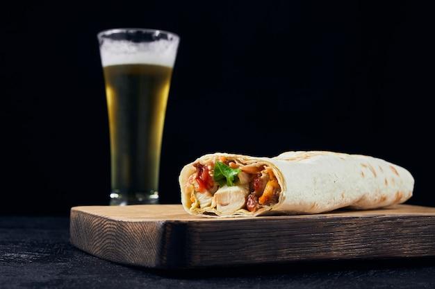 Фаст-фуд и холодное светлое пиво. шаурма размещена на деревянной доске на барной стойке с копией пространства.