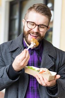 ファーストフードと食事のコンセプト – 通りで食べ物を奪う若い男。
