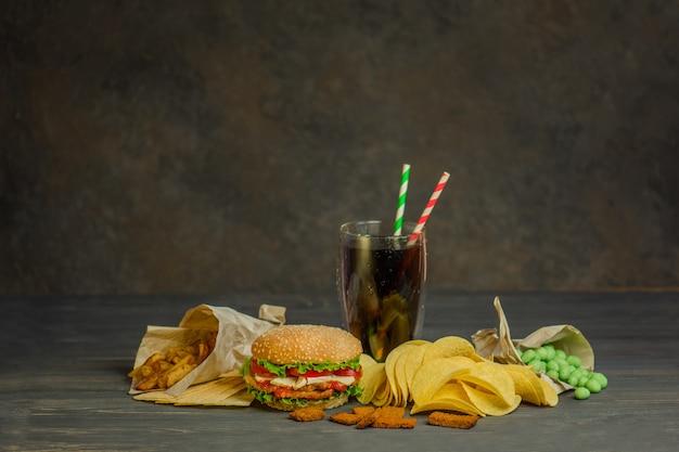 ファーストフードとスナックのコンセプト。不健康な栄養ハンバーガー、ポテトフライ、コーラと2本の紙管。