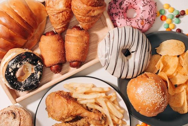 패스트 푸드와 건강에 해로운 식사 개념 - 흰색 테이블에 패스트 푸드 스낵과 콜라 음료를 가까이