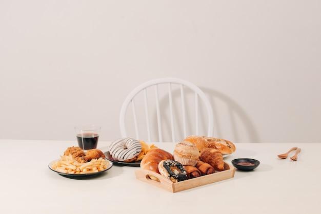 패스트푸드와 건강에 해로운 식사 개념 - 햄버거나 치즈버거, 튀긴 오징어 링, 감자튀김, 음료, 케첩을 나무 탁자에 올려 놓습니다.