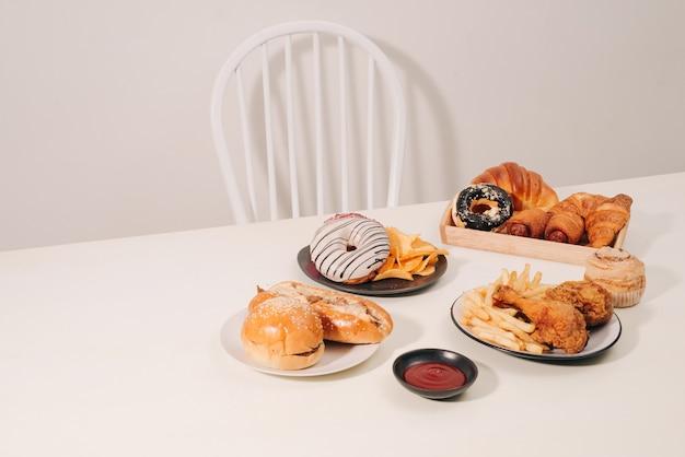 ファーストフードと不健康な食事のコンセプト-ハンバーガーまたはチーズバーガー、揚げイカのリング、フライドポテト、飲み物、ケチャップを木製のテーブルにクローズアップ