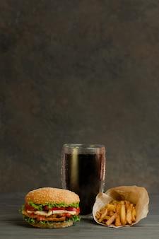 ファーストフードと不健康な食事の概念。美味しくて食欲をそそるハンバーガー、コーラ、フライドポテト