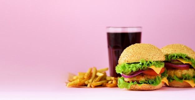 Fast food banner. juicy meat burgers, french fries potatoes and cola drink on pink background. take away meal. unhealthy diet concept