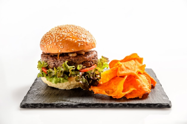 Fast food. a big burger with sweet potato chips. .