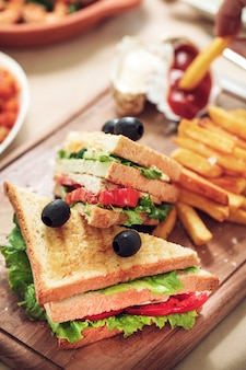 Fast food board with club sandwiches and french fries.