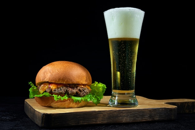 Fast food and cold light beer. burger placed on a wooden board on bar counter with copy space.