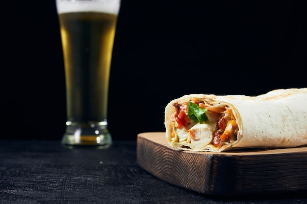 Fast food and cold light beer. shawarma placed on a wooden board on bar counter with copy space.