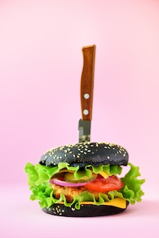 Fast food concept. juicy black burger with knife on pink background. take away meal. unhealthy diet frame with copy space