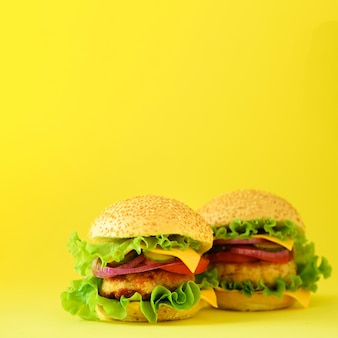 Fast food concept. square crop. juicy homemade hamburgers on yellow background. take away meal. unhealthy diet frame