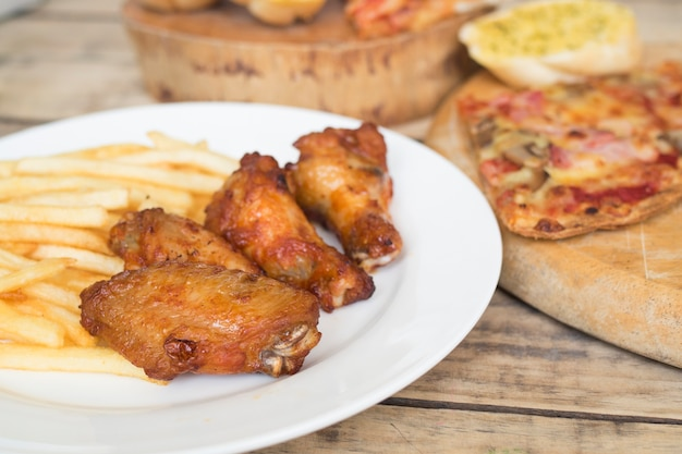 Fast food, crispy chicken wings,bread,french fries and pizza on wood background.