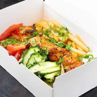 ファーストフードの配達。ギリシャのスブラキ、サラダ、ジャイロは、テーブルの上のリサイクル可能な紙皿で提供されるファーストフードレストランからメニューを奪います。