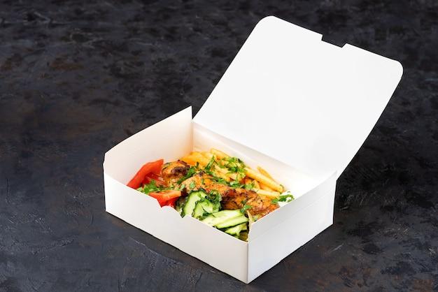 Доставка фастфуда. греческие сувлаки, салат и гирос на вынос из ресторана быстрого питания, которые подаются на столе в перерабатываемых бумажных тарелках. Premium Фотографии