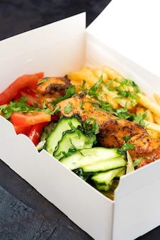 Доставка фастфуда. греческие сувлаки, салат и гирос на вынос из ресторана быстрого питания, которые подаются на столе в перерабатываемых бумажных тарелках.