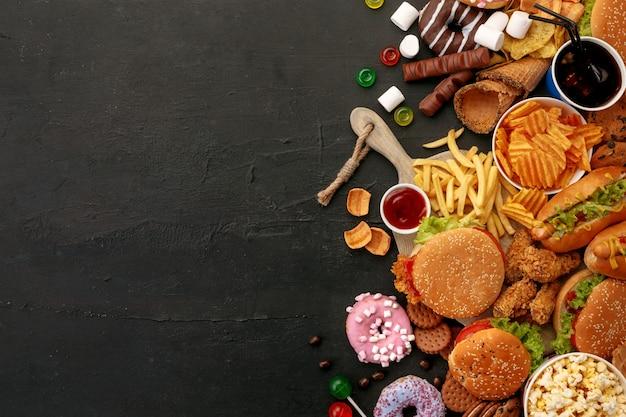 검은 돌 배경에 패스트 푸드 요리입니다. 햄버거, 소스, 감자 튀김, 도넛, 콜라, 과자, 아이스크림 및 비스킷을 포함한 건강에 해로운 세트를 제거하십시오. 부적절한 영양 섭취로 인한 다이어트 유혹. 프리미엄 사진