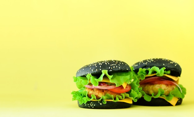 Fast food frame. delicious meat burgers on yellow background. take away meal. unhealthy diet concept with copy space