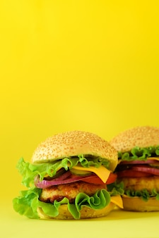 Fast food frame. delicious meat burgers on yellow background. take away meal. unhealthy diet concept