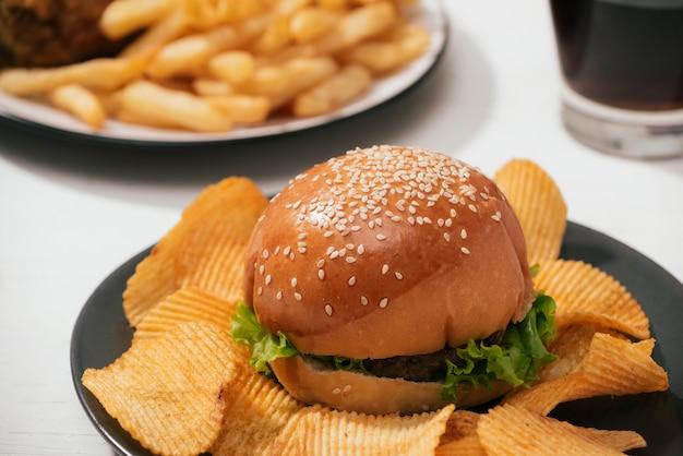 揚げたクリスピーチキンとフライドポテトをセットしたファーストフードハンバーガー、サイドにアイスコーラ