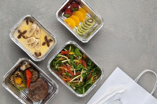 Фаст-фуд в коробке из фольги на сером фоне. здоровая еда крупным планом. доставка из ресторана набора здорового питания