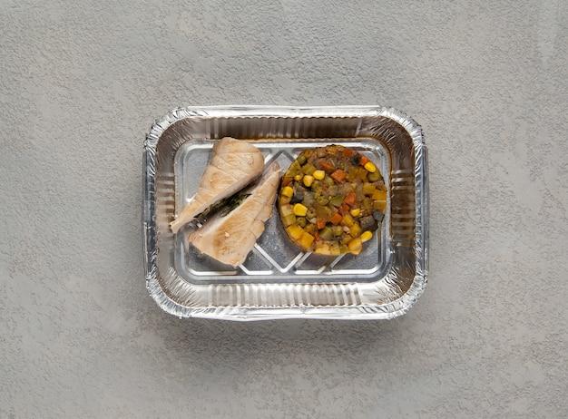 회색 배경에 호일 상자에 패스트 푸드. 건강에 좋은 음식을 닫습니다.
