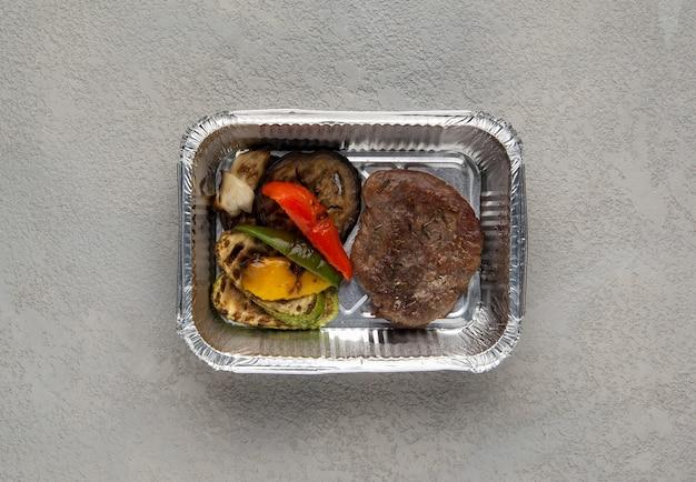 회색 배경에 호일 상자에 패스트 푸드. 건강에 좋은 음식을 닫습니다