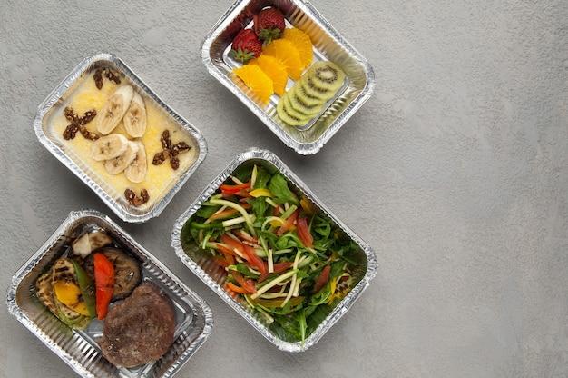 Фастфуд в фольгированной коробке на сером фоне доставка из ресторана набора здорового питания