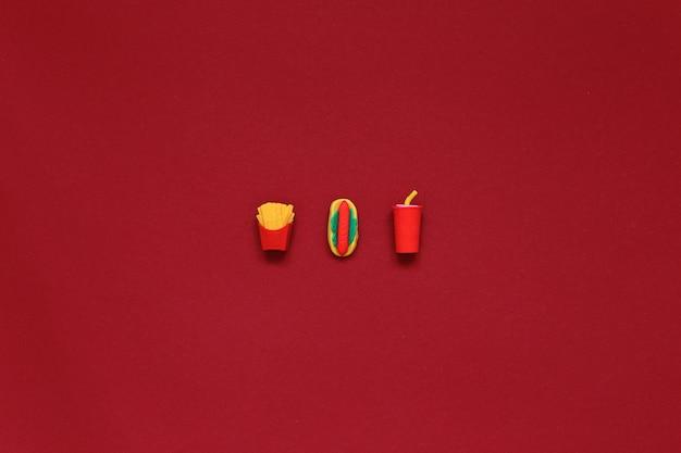 Фаст-фуд лежит на красном фоне. еда на заднем плане. фото высокого качества
