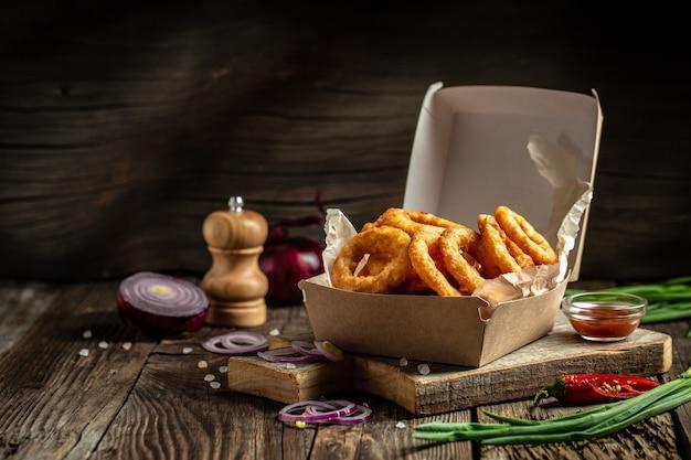 Луковые кольца быстрого питания в бумажной коробке на деревянном столе