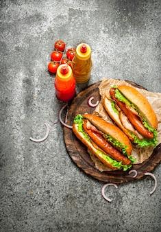 패스트 푸드 메뉴. 소박한 테이블에 허브, 케첩, 핫 겨자와 핫도그 쇠고기 바베큐.
