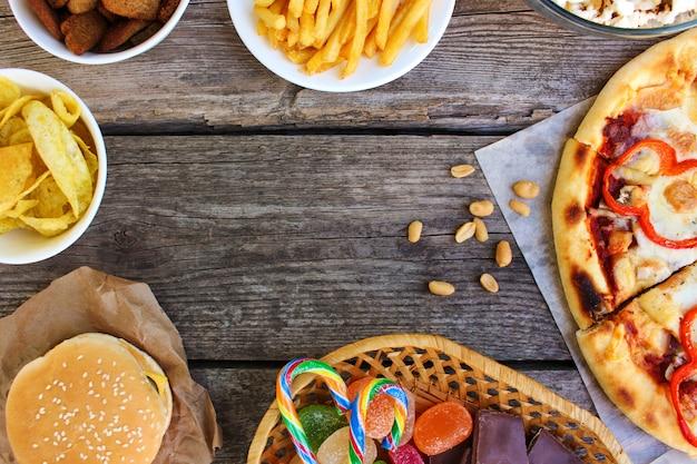Фаст-фуд на старых деревянных фоне. концепция нездоровой пищи. вид сверху.