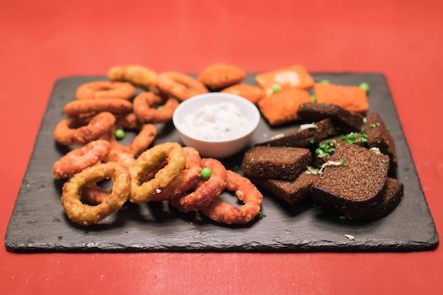 어두운 탁자 위에 있는 패스트푸드 양파 링 감자와 프라이드 치킨 소스