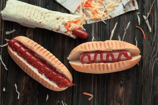ファーストフード。木製テーブルの上のピタパンとホットドッグのソーセージ