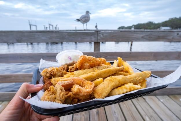 Морепродукты быстрого приготовления. хрустящая рыба, креветки и чипсы. жареные морепродукты, картофель фри, дольки лимона в одноразовой посуде в ресторане в порту.