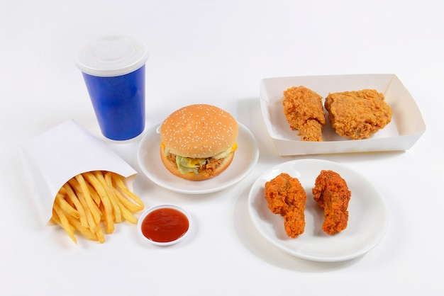 Fast food set containing burgers, fried chicken, french fries and soft drink on white back