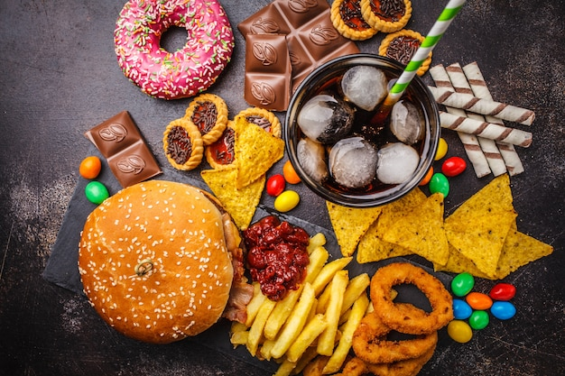Fast food and sugar. burger, sweets, chips, chocolate, donuts, soda, top view.