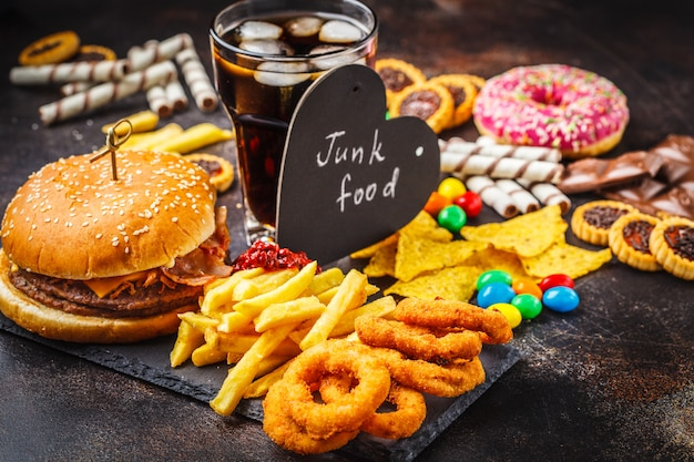 Fast food and sugar. burger, sweets, chips, chocolate, donuts, soda.