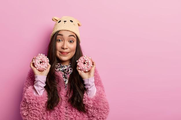Fast food, concetto di mangiare malsano. attraente posa femminile con deliziose ciambelle, suggerisce di assaggiare dolci fatti in casa, ha un debole per i dolci, indossa capispalla. tono pastello