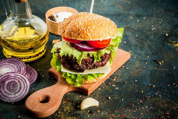 Fast food. unhealthy food. delicious fresh tasty burger with beef cutlet, fresh vegetables and cheese on dark blue concrete surface. copy space