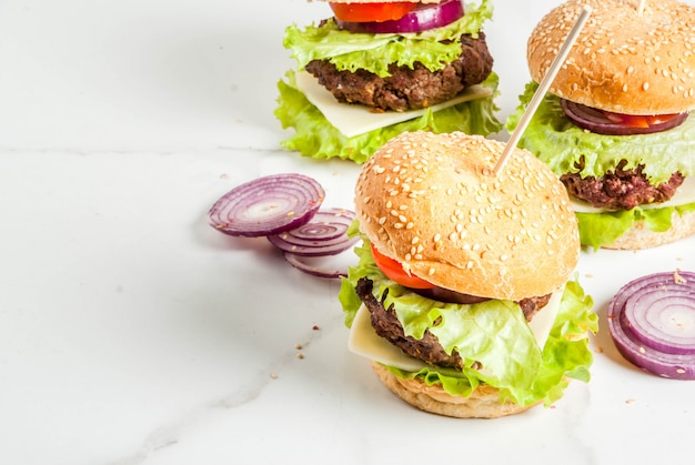 Fast food. unhealthy food. delicious fresh tasty burgers with beef cutlet, fresh vegetables and cheese on white . copyspace