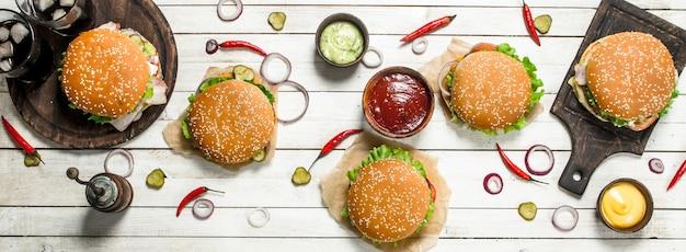 Быстрое питание. различные бургеры с говядиной и свежими овощами. на белом деревянном столе.