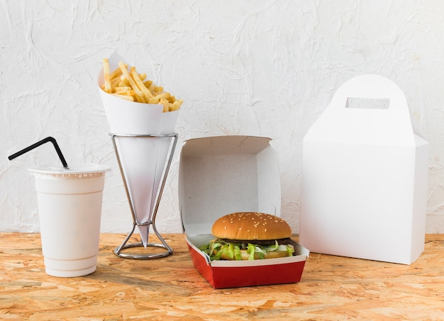 Fast food with disposal cup and food parcel mock up on wooden desk
